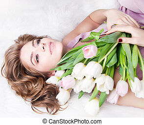 Dreamy pretty girl with bunch of fresh tulips lying in bed