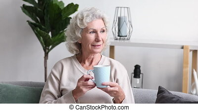 Dreamy relaxed older 70s retired beautiful woman drinking ...