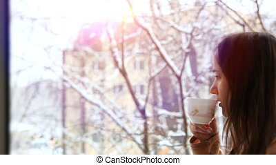 Dreamy thoughtful beautiful brunette with cup of hot beverage looks at window it snows. HD. 1920x1080