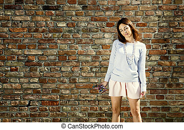 Dreamy woman against wall