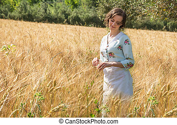 Dreamy woman in 40s clothes in a wheat field