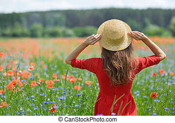 Dreamy woman in red dress and hat in beautiful herb flowering poppy field. Vintage elegant romantic look. concept of lovely summer