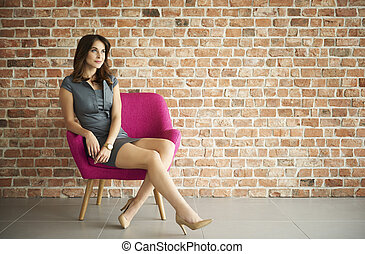 Dreamy woman on the brick wall