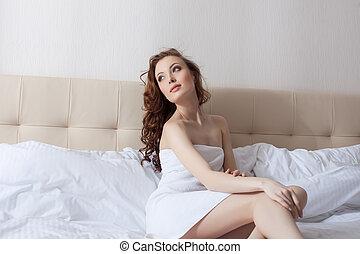 Dreamy woman posing in hotel bedroom