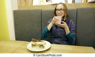 Dreamy young girl in glasses drinking hot scandinavian tea with blueberries and mint from a pink cup and relaxing in cafe, smiling and looking at camera. The cake called Swedish Espresso on a plate.