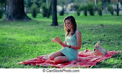 dreamy young girl in the park reading a book