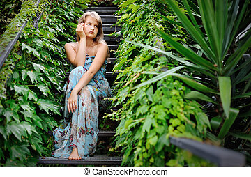 young girl sitting on the stairs in a garden covered with ivy