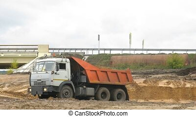 Dredger puts earth in dump truck KAMAZ closeup