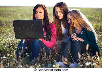 drei, junger, schöne frau, mit, a, laptop, sitzen, in, der, feld, auf, himmelsgewölbe, hintergrund