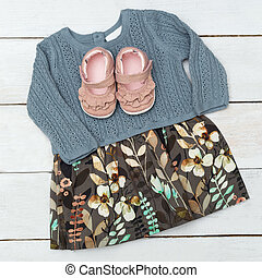 Dress for a little girl leaf print and shoes on wooden background. Flat lay