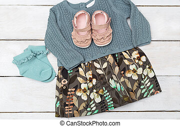 Dress for a little girl leaf print on wooden background. Flat lay