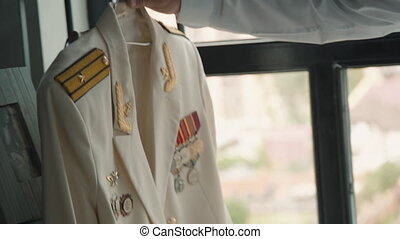 Dress for army in the hand of man for ceremony event. Person takes hanger with ceremonial tunic to prepare for festive celebrations. Against background of window in daylight model prepares jacket with medal and award for victory. Patriotic clothing.