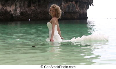 dressed bride walks in shallow azure water - young beautiful...