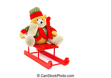 Dressed Christmas bear on red wooden sleigh