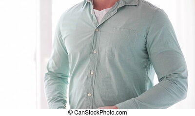 close up of man unbuttoning his shirt at home