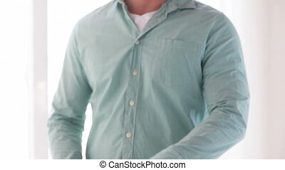 man unbuttoning his sleeve at home - dressing, clothing and...