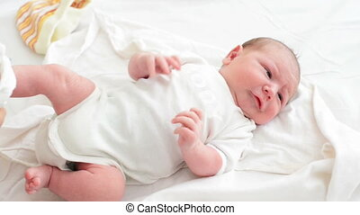 Dressing Newborn Baby - Nursing mother dressing her newborn...