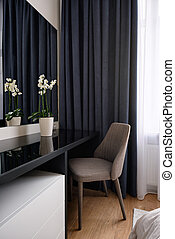 Dressing table with a mirror and flowers in the room. Boudoir table. Details of interior bedroom for girls and make-up, hairstyles with mirror.
