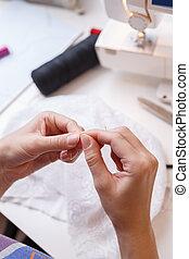 Dressmaker cuts thread in fabric