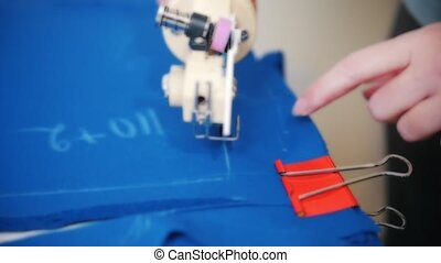 Dressmaker cutting cloth with the tool. Close up shot