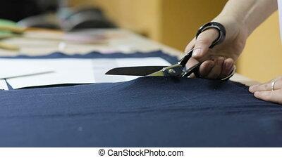 Dressmaker cutting fabric. Girl customize template - Young...