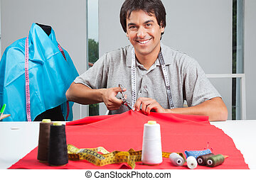 Dressmaker Cutting Fabric - Portrait of young clothing...