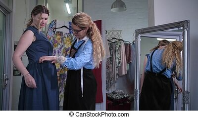 Skillful seamstress cutting out pocket in sewing dress while working with female customer in design workshop. Woman client standing at large mirror fitting dress while stylist cutting through pocket