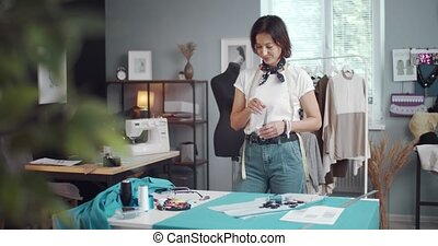 Thoughtful dressmaker in casual clothing standing with scissors in hands and looking at blue fabric that lying on desk. Beautiful woman checking all measurements before cutting cloth.