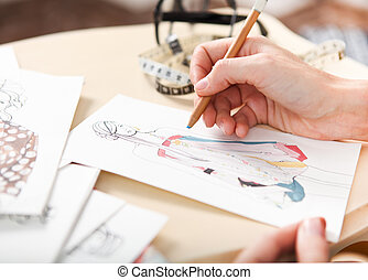 Dressmaker is drawing a fashion sketch. Close up of the ...