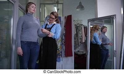 Cheerful clothes designer taking measurements of female customer in sewing atelier. Middle aged women standing at large mirror, dressmaker working with measuring tape before tailoring clothing