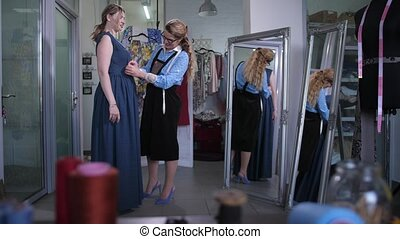 Satisfied female customer standing in front of mirror trying on dress at sewing stage in design workshop studio. Professional seamstress making fit of dress on client's figure using pins in atelier