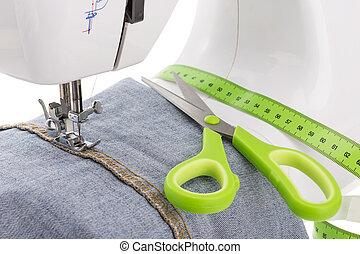 Dressmaker scissors, sewing machine and meter. Textile close-up.