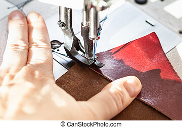 dressmaker sewing leather on sewing machine