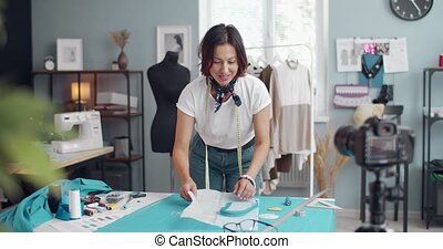 Professional female dressmaker standing at own atelier and recording video on digital camera for her blog. Happy woman sharing all secrets of sewing stylish clothes.