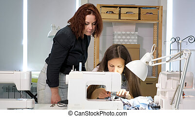 Seamstress teacher controls looks how student sew on sewing machine in workshop.