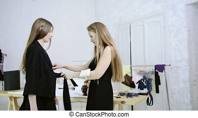 Dressmaker trying the product to the client in the workshop.