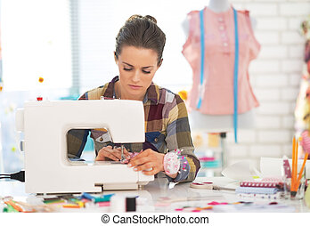 Dressmaker woman working with sewing machine