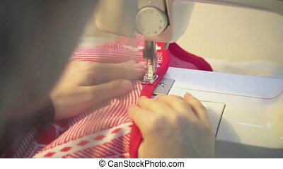 dressmaker works on the sewing machine close-up