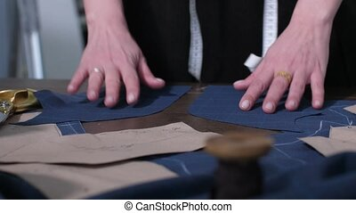 Dressmaker's hands laying out cut pattern on table -...