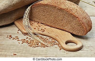 drewniany stół, nagniotek, chleb żytni