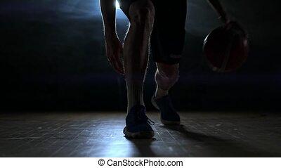 Dribbling basketball player close-up in dark room in smoke...