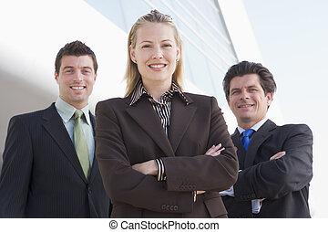 drie, businesspeople, staand, buitenshuis, door, gebouw, het...