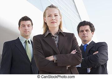 drie, businesspeople, staand, buitenshuis, door, gebouw