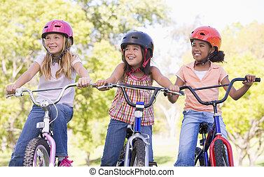 drie, jonge, bicycles, buitenshuis, vriendinnetjes, het glimlachen