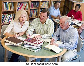 drie mensen, in, bibliotheek, met, notepads, (selective, focus)