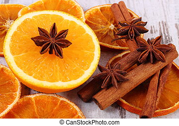 Dried and fresh orange with spices on old wooden background