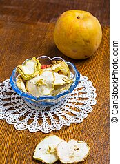 Dried apples in glass bowl on wooden table