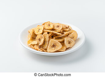 Dried bananas in a white plate on a light background.