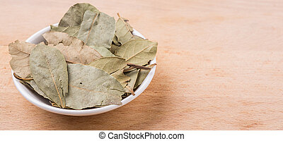 Dried Bay Leaves - Dried bay leaves in white bowl on wooden...