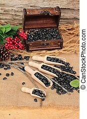 Dried black beans on wood background.